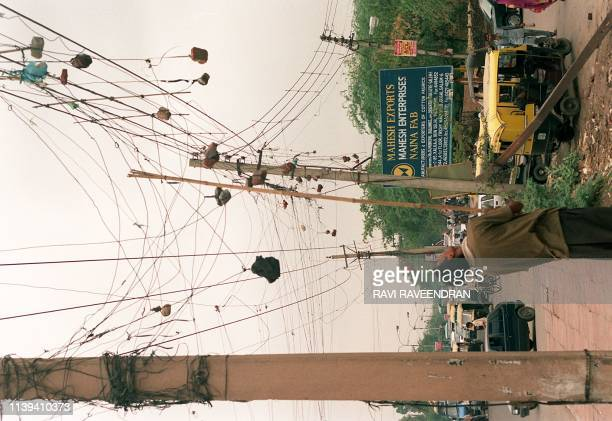 A young man steals electricity from an already heaviliy illegally wired main power line 10 July in the Kalkaji locality of the Indian capital A...