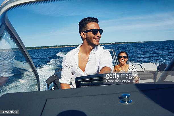 Young man steering boat with woman in background, Gavle, Sweden