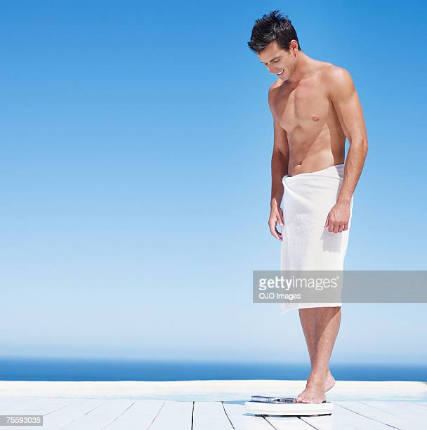 young man stepping on a scale - wrapped in a towel stock pictures, royalty-free photos & images