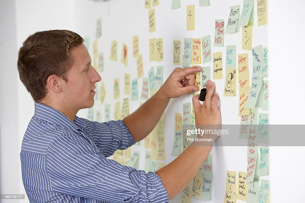 Young man sticking adhesive note on wall : Stock Photo