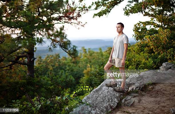 young man stops to look out at an overlook while hiking at oak mountain state park in birmingham, alabama. - pelham alabama stock pictures, royalty-free photos & images