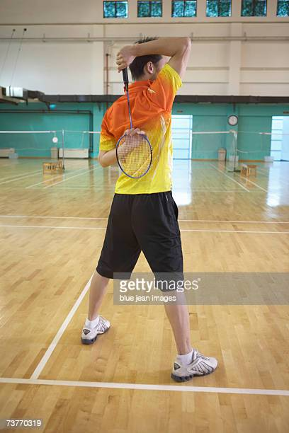 Young man stretches his arms before playing badminton.