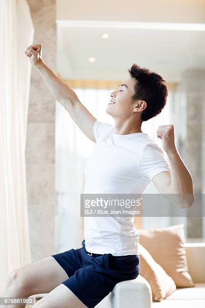 Young man stretching at home