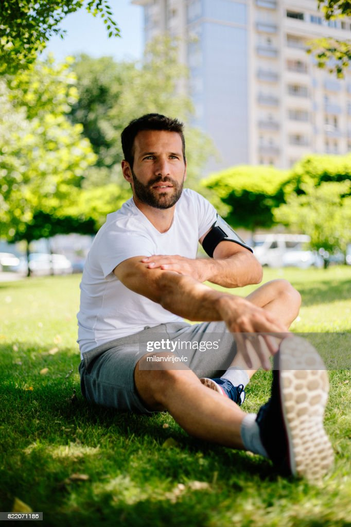 Young man stretching before training in nature : Stock Photo