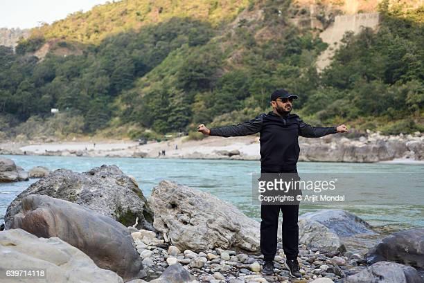 Young Man Stretching Hands at Riverside of Ganga, Rishikesh