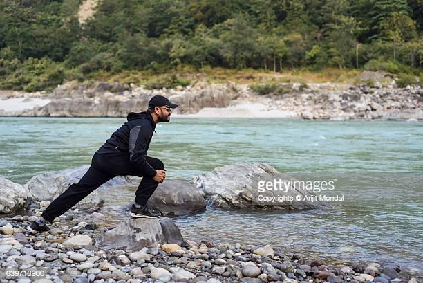 Young Man Stretching His Hamstrings At Riverside of Ganga, Rishikesh