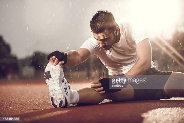 Jeune homme s'étirant sa jambe sur la pluie.