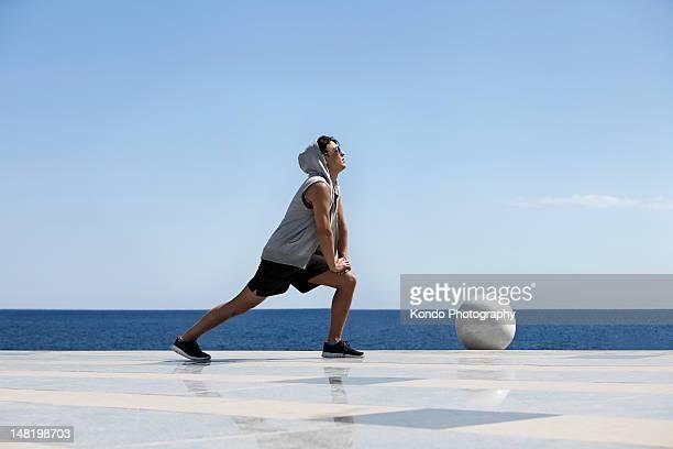 若い男性のストレッチ海の近く - スポーツウェア ストックフォトと画像