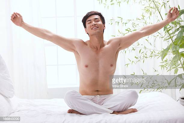Young man stretching on bed