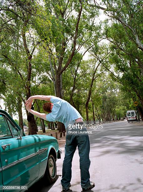 Young man stretching outside car, rear view