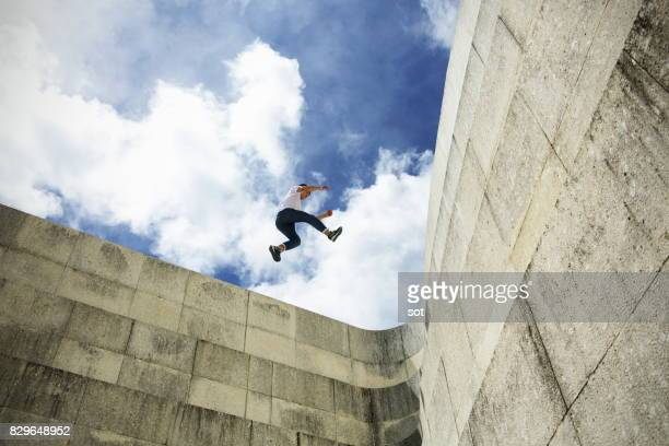 young man stride jumping  on concrete wall - risk stock pictures, royalty-free photos & images