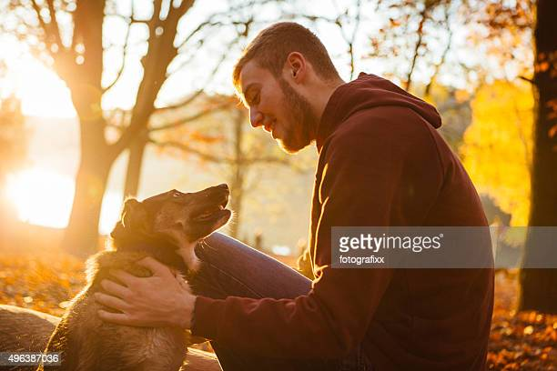 young man strokes his small Mixed-breed dog