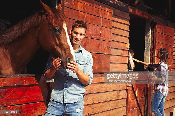 Young man stroking a brown horse.