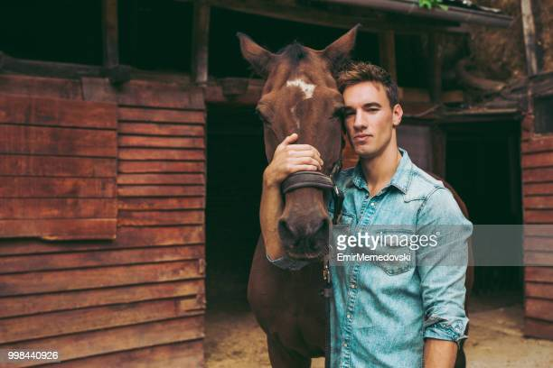Young man stroking a brown horse