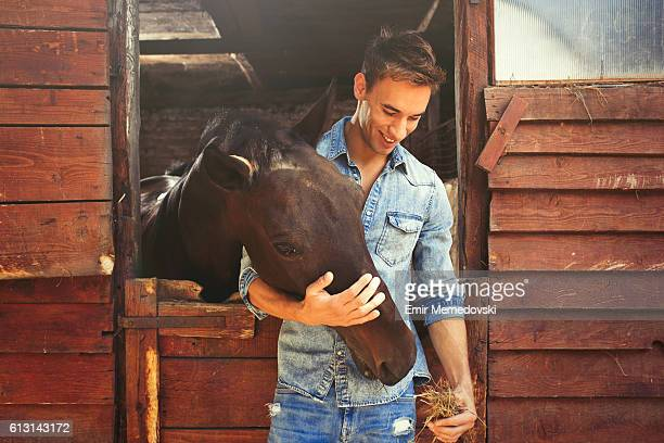 Young man stroking and feeding a brown horse.