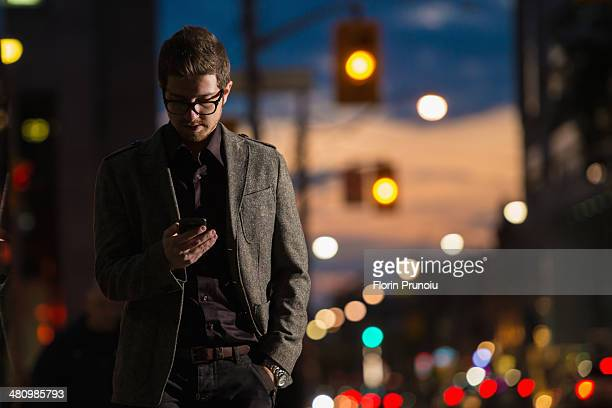 Young man strolling down street looking at mobile phone, Toronto, Ontario, Canada
