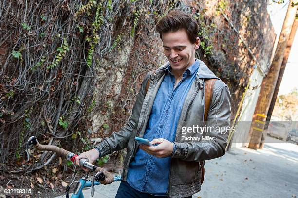 young man strolling with cycle on sidewalk reading smartphone texts - monrovia california stock pictures, royalty-free photos & images