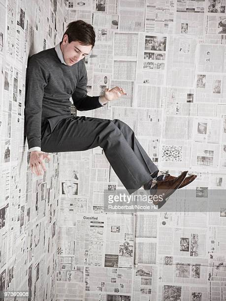 Young man stuck to wall covered with newspapers, studio shot