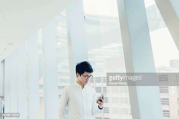 Young man student studying on smartphone