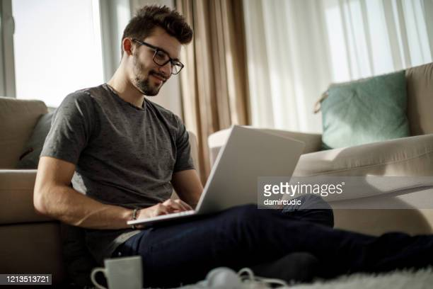young man studying and working on laptop at home - young men stock pictures, royalty-free photos & images
