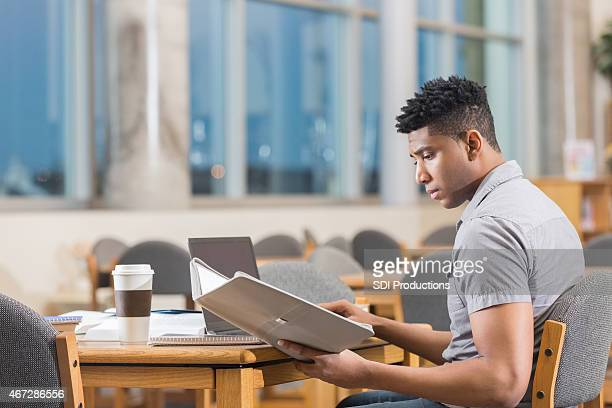 Young man studying for test after hours in library
