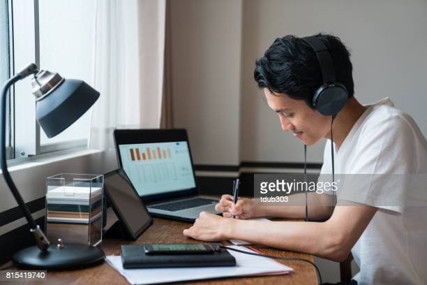 Young man studying in his room while listening to music