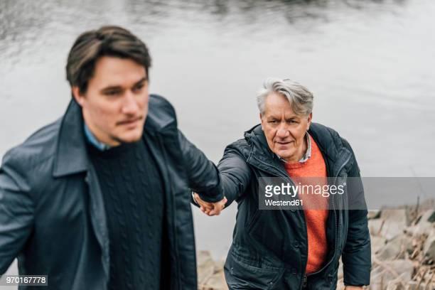 Young man supporting senior man at the riverside