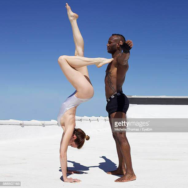 Young Man Supporting Woman Doing Handstand On Desert
