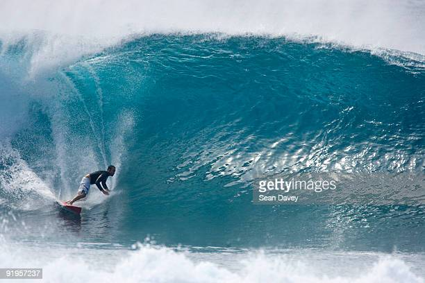 a young man surfing a big wave at pipeline, on the north shore of oahu, hawaii. - north shore stock photos and pictures