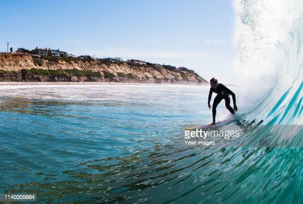young man surfing a wave, encinitas, california, usa - surfer stock-fotos und bilder
