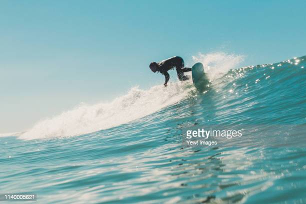 young man surfing, low angle view - surf ストックフォトと画像