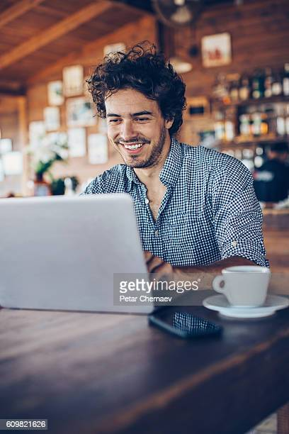 Young man surfing the net in cafe