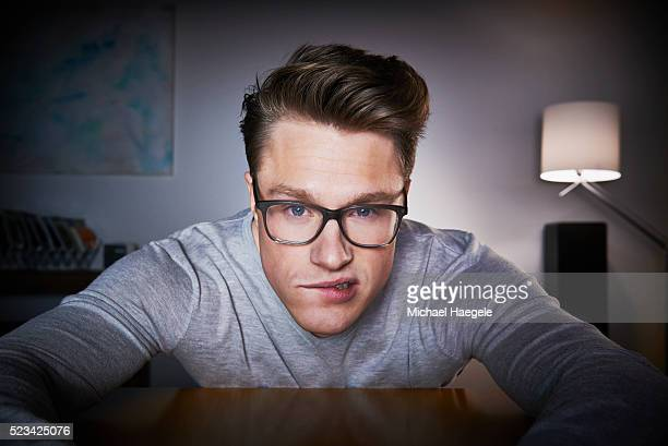 young man surfing the web - biting lip stock pictures, royalty-free photos & images