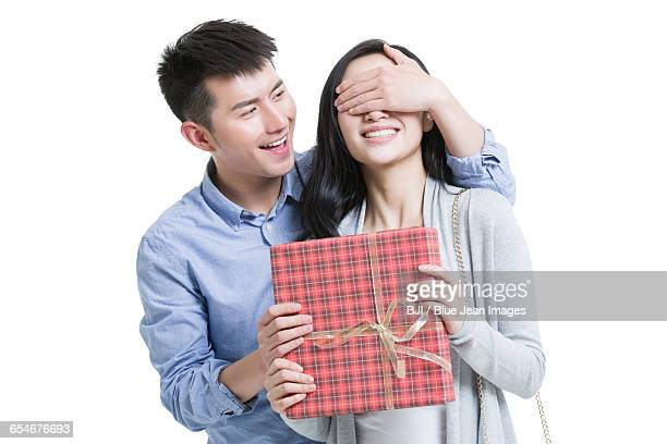 Young man surprised girlfriend with a gift