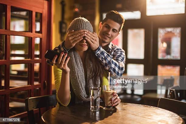 Junger Mann überraschend seine Freundin in einem Café.