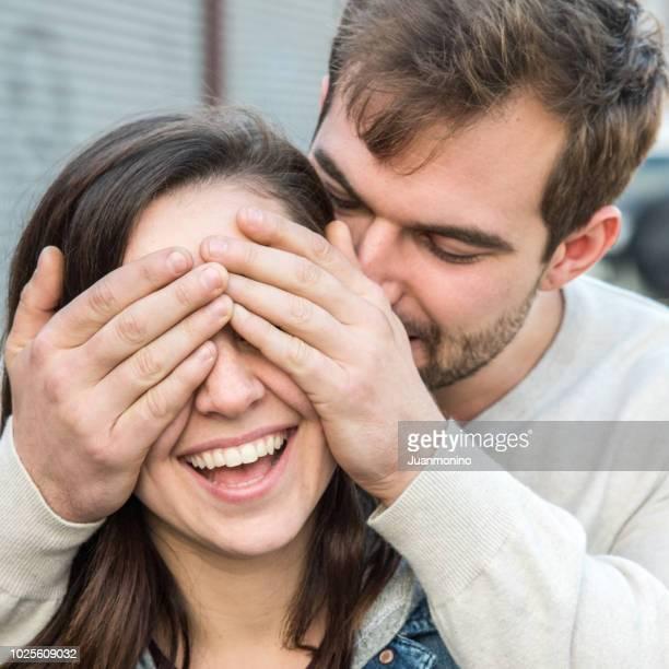 junger mann seine freundin überraschen - augen zuhalten stock-fotos und bilder