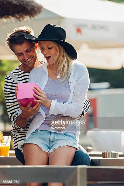 young man surprising his girlfriend with a gift at outdoor cafe - gift lounge stock-fotos und bilder