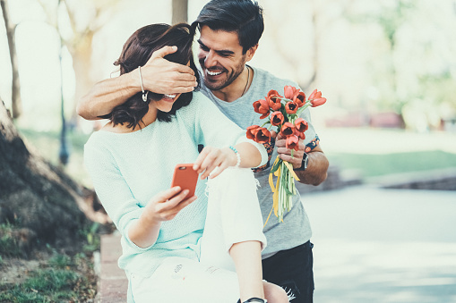 Young man surprising his girlfriend with bouquet of tulips 1088774826