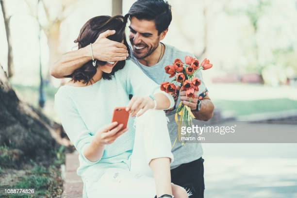 young man surprising his girlfriend with bouquet of tulips - valentines day stock pictures, royalty-free photos & images