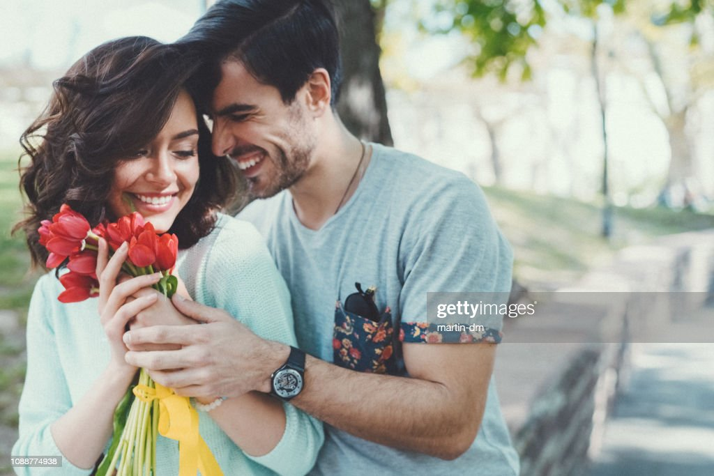Young man surprising his girlfriend with bouquet of tulips : Stock Photo