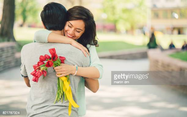 Young man surprising his girlfriend with bouquet of tulips
