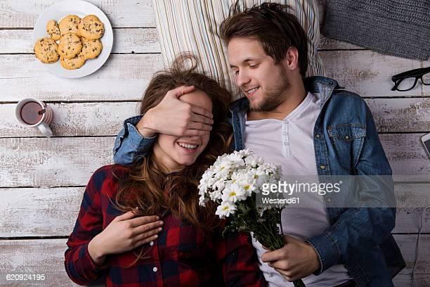 young man surprising his girlfriend with flowers - ギフトラウンジ ストックフォトと画像
