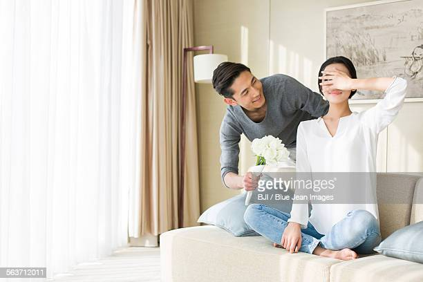Young man surprising wife with flowers