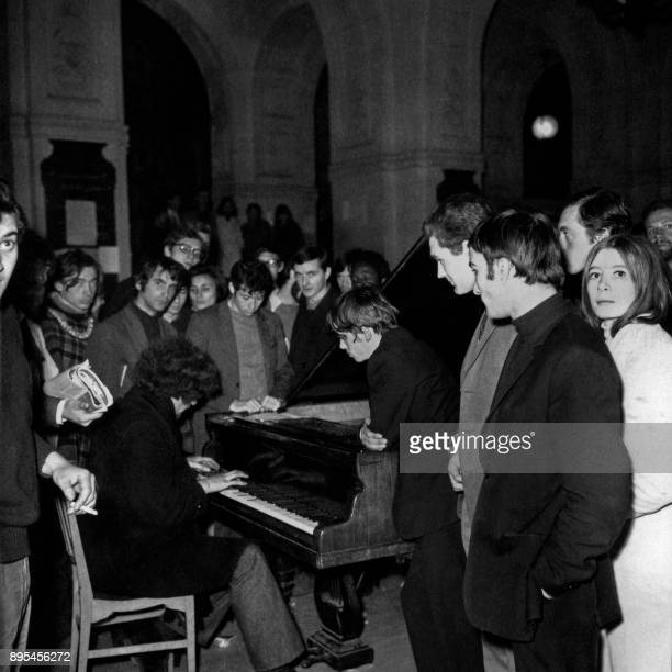 A young man surrounded by student protesters plays piano at the Sorbonne university on May 20 during the May 1968 events in France / AFP PHOTO /