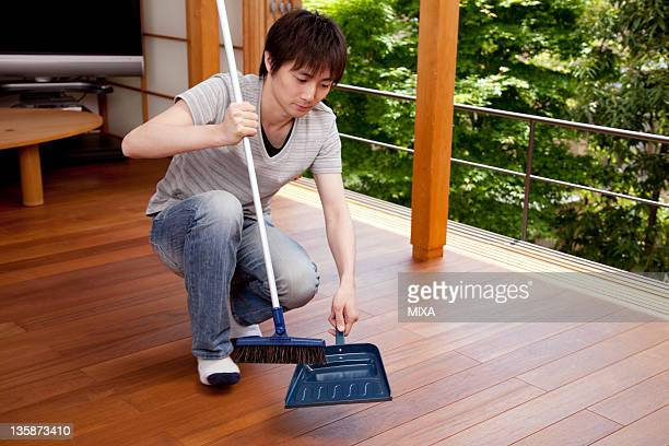 Young man sweeping floor with broom and dustpan