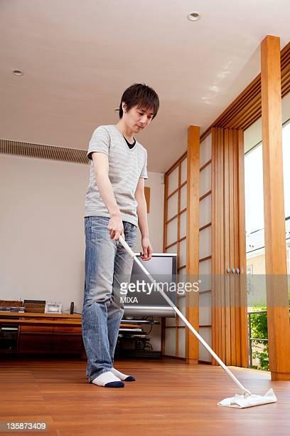 Young man sweeping floor with floor mop