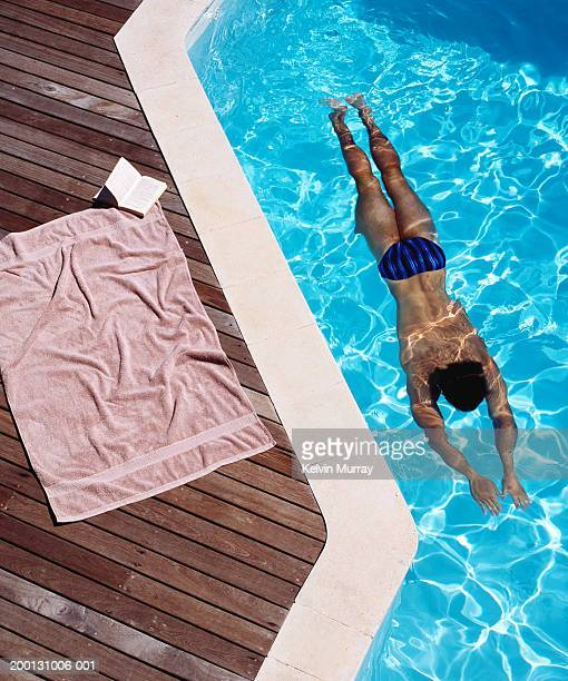 Young man swimming, towel and book at pool edge, elevated view