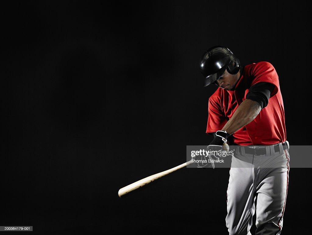 Young man swinging baseball bat : Stock Photo