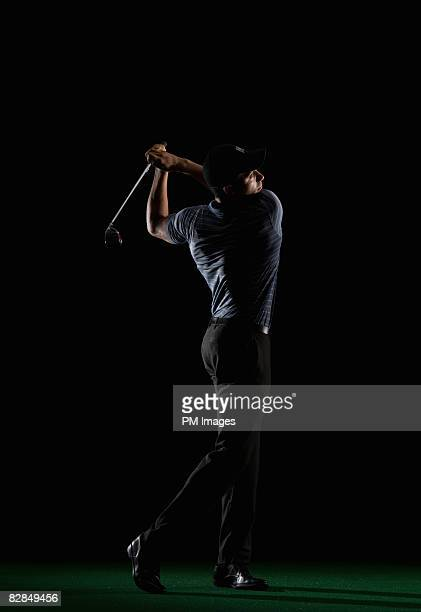 young man swinging golf club - golfer stock pictures, royalty-free photos & images