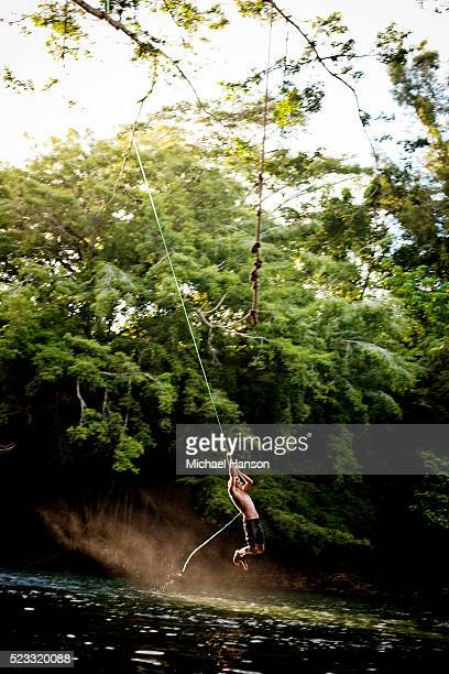 Young man swinging on rope swing